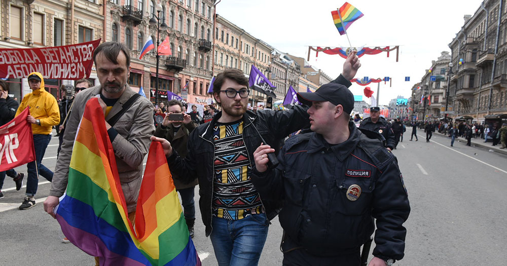 A pair of male Russian activists marching for LGBT rights at the head of a parade are questioned by a policeman