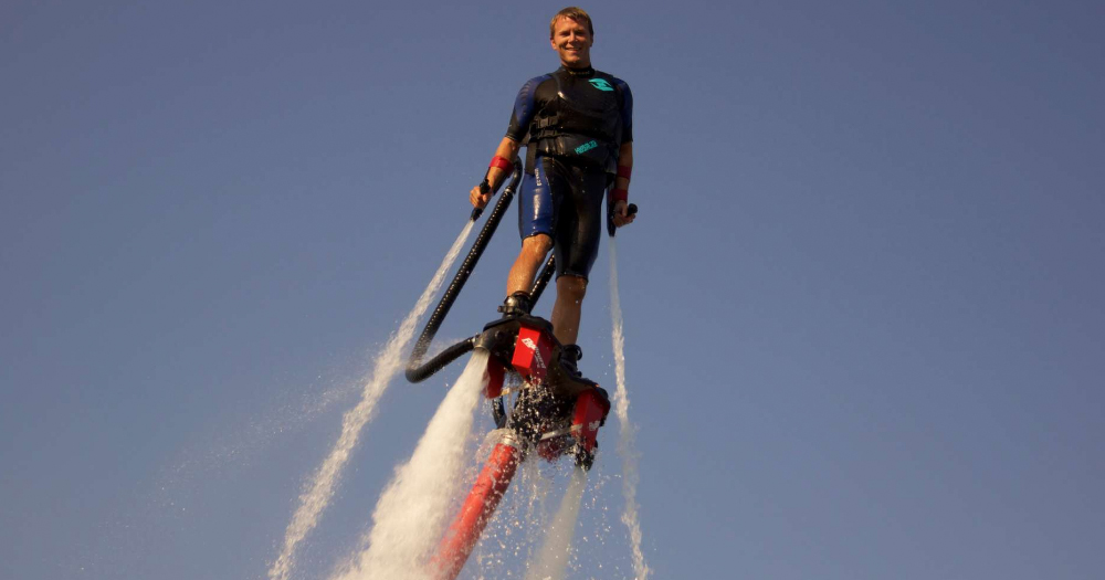 A man is propelled into the air on a jet ski at a water sports facility.