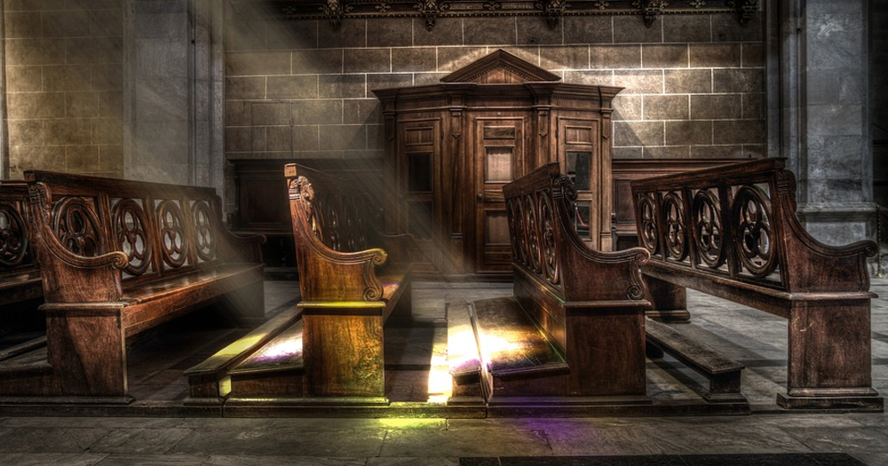 Image of light shining through a church on the pews.