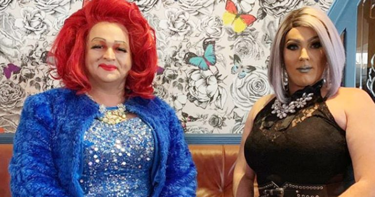 Two drag queens sit against a patterned backdrop