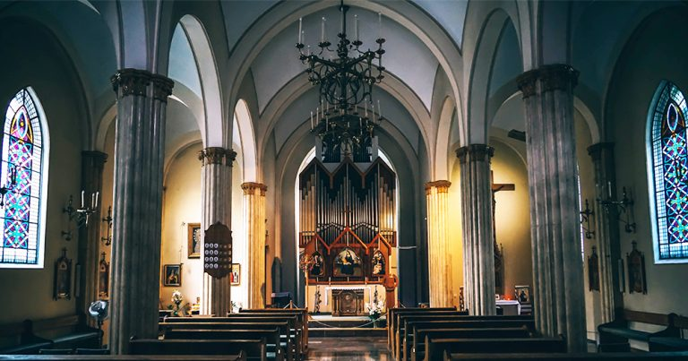 The dark interior of a church with lights either side of the altar
