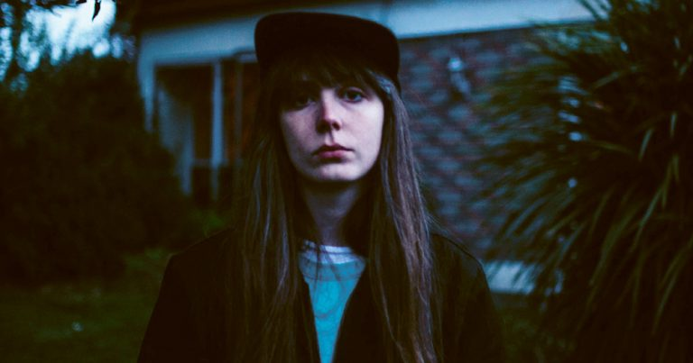 Kate Dolan wearing a cap stands outside a suburban house in the evening