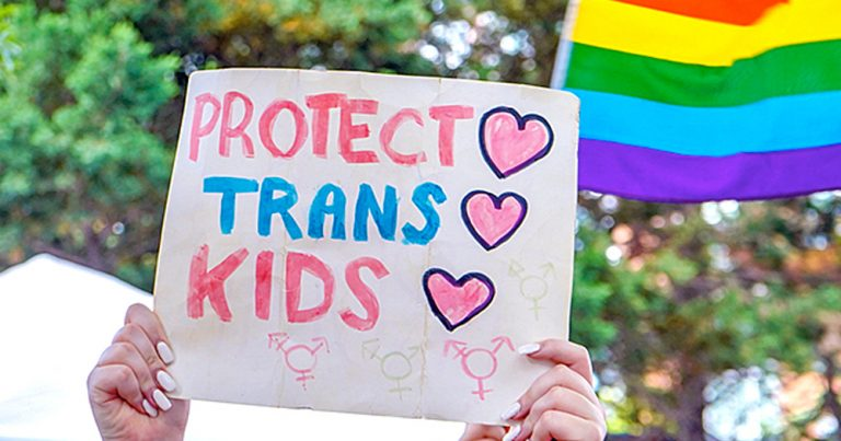 A banner that reads 'Protect Trans Kids' and a rainbow flag in the background.