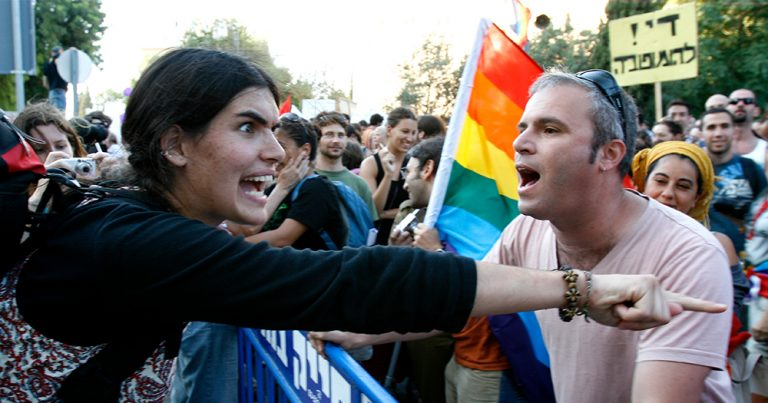 An irate woman screams with pointed finger at LGBT+ people marching in a gay pride parade holding rainbow flags protesting homophobic attacks