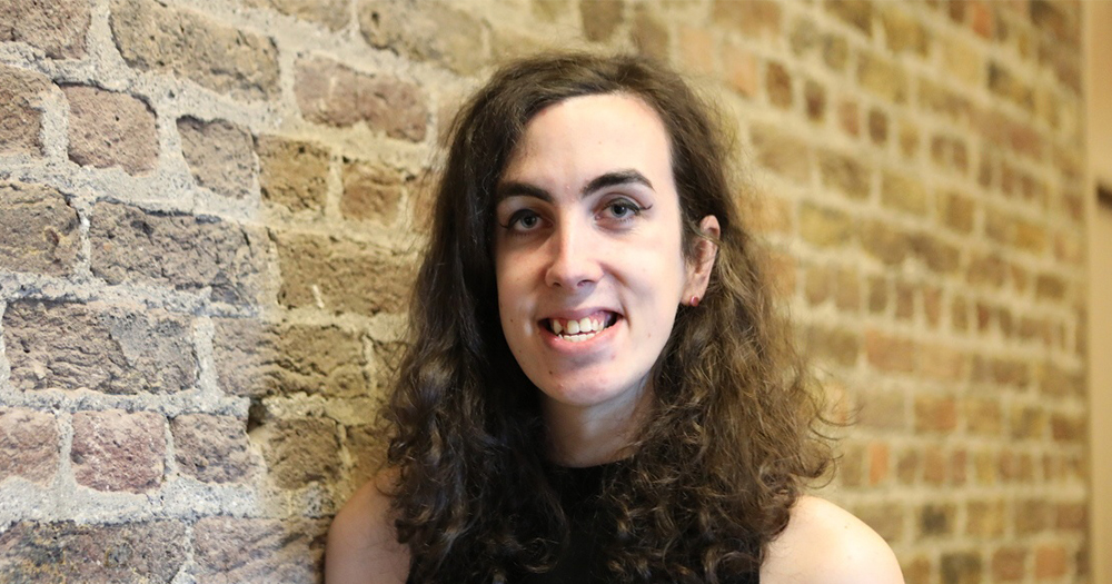 Young trans woman Karla O'Brien standing in a sleeveless dress standing beside a brick wall