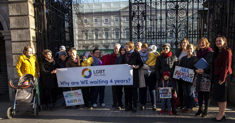 A group of same-sex parents, their children and a group from LGBT Ireland hold a banner while protesting outside the Dáil
