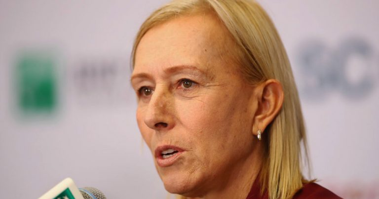 A close up of Martina Navratilova speaking into a microphone at a press conference
