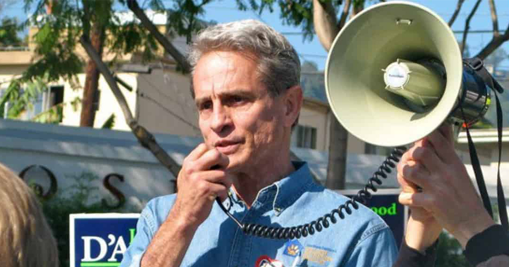 Ed Buck, an older man, speaking into a megaphone at a political rally