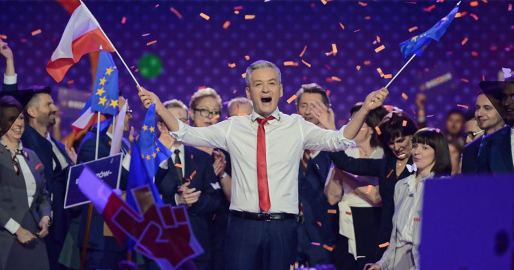 Robert Biedron waves a Polish flag and European flag as his party members stand in the background as they celebrate the launch of their party