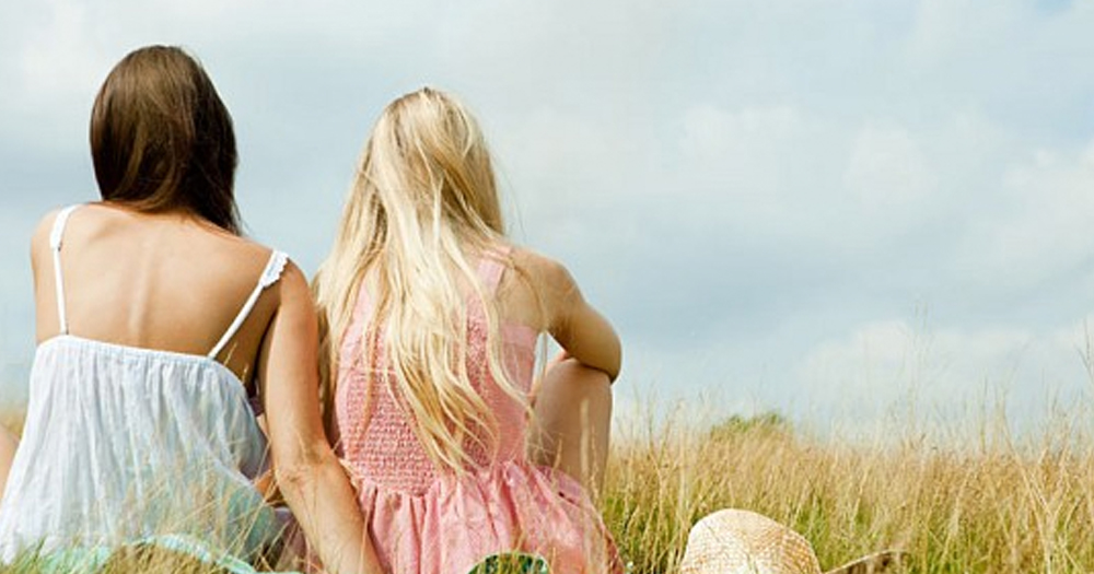 Two women sit together with their backs to the camera in an open field.