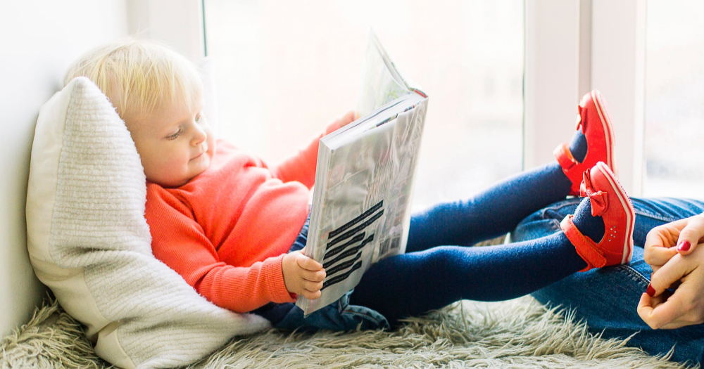 A toddler reads a book on a pillow.