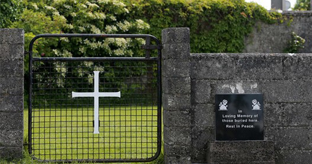 Entrance to Tuam featuring a gate with a christian cross on it and a sign reading 'in loving memory of those who died here. rest in peace.' Published during fight for rights of mother and baby home surivors.