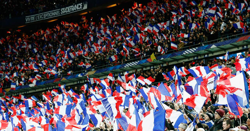 French football fans in the auditorium holding flags