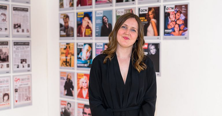 Managing Editor Lisa Connell at an exhibition in front of a wall of GCN covers