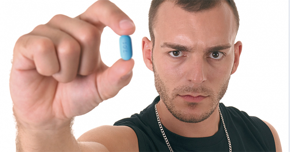 Man with angry expression holds up Truvada PrEP pill