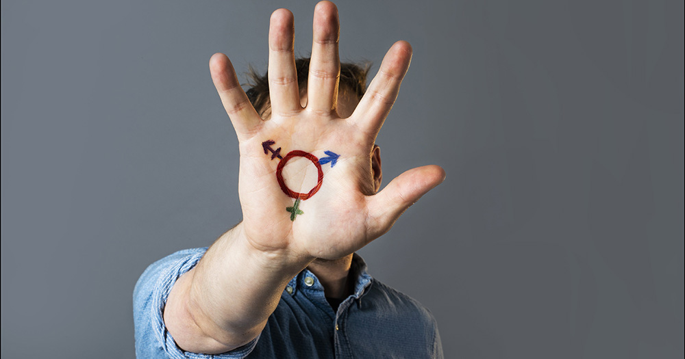 Linklaters becomes the first 'magic circle' law firm to pay for gender confirmation surgery. In this image, a man raises his hand with a transgender pride symbol painted on his palm.