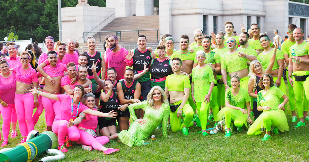 A large Mardi Gras group in bright clothes pose with drag queen Panti in a park