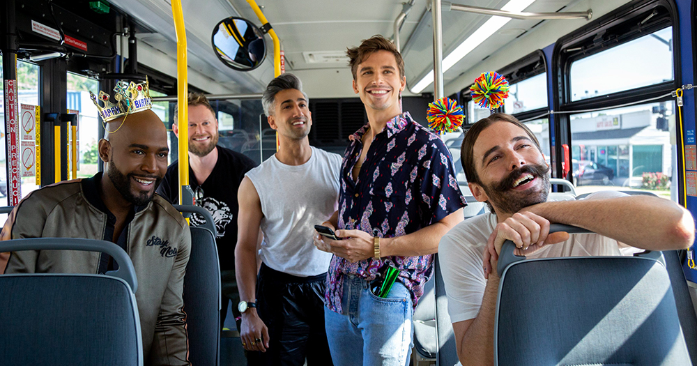 The cast of Queer Eye - five men on a bus dressed as if going to a birthday party