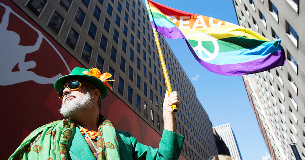 A man dressed in green at Staten Island St Patrick's Day parade holds a rainbow flag