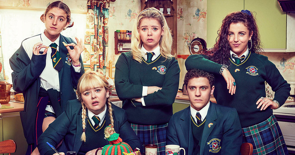 The five lead characters from Derry Girls all dressed in school uniforms pose comedically around a kitchen table