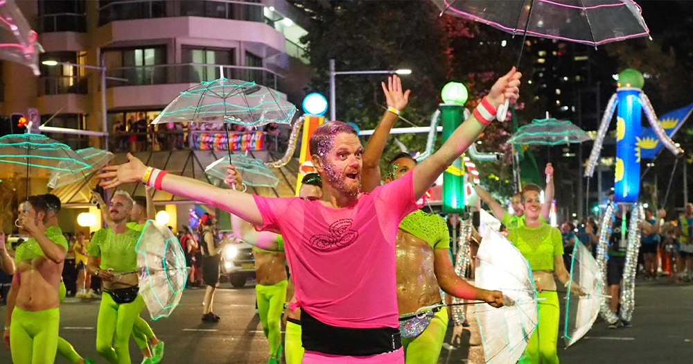 The Sydney Queer Irish Mardi Gras team dance dressed in tight illumines clothes while holding umbrellas