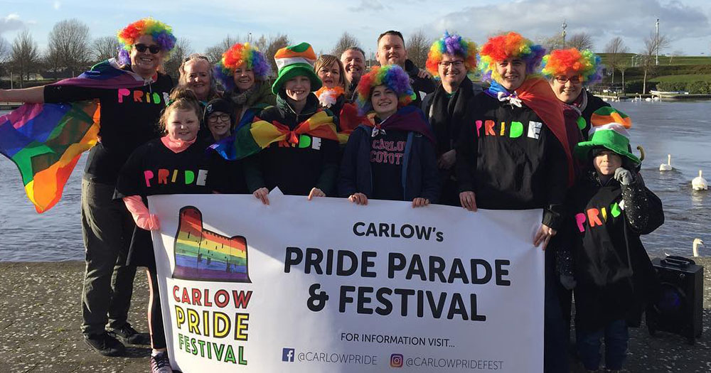 Group of rural organisers for Carlow Pride donned in rainbow clothing holding up sign which states: 'carlow pride parade & festival""
