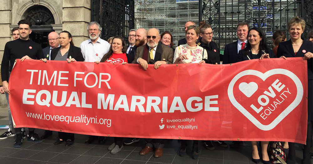 Love Equality members from Northern Ireland holding up red banner reading: '