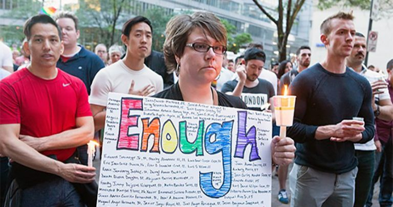 "People at a vigil, a woman is holding a sign which reads ""Enough"", demanding demanding hate crime legislation"