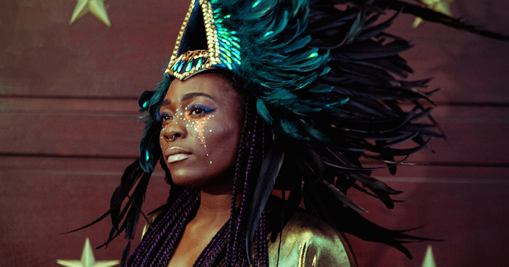 In a promo for Nightclubbing, a young black woman wears a huge feathered headpiece and looks away into the distance