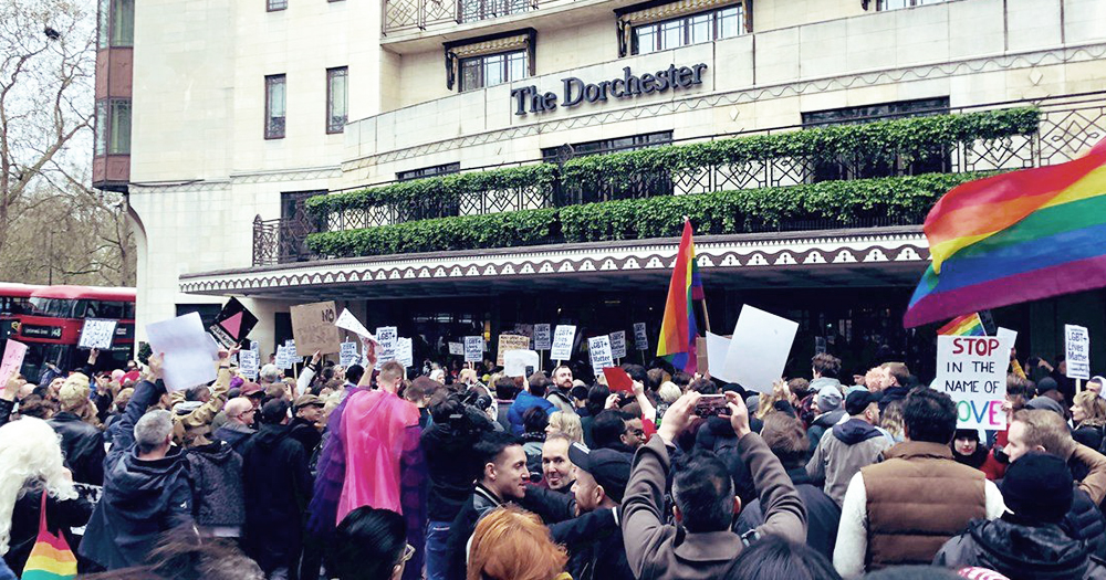 A group of protestors outside The Dorchester Hotel holding rainbow flags
