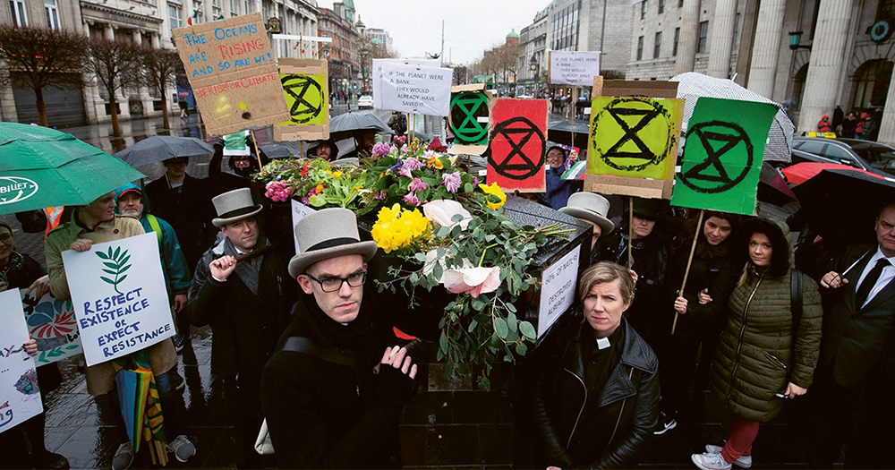 Climate crisis protestors in Dublin City centre carrying a coffin representing ecological death