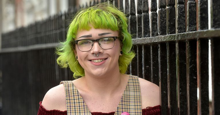 At the launch of the Youth Work Ireland resource, a smiling young trans woman stands by a metal railing