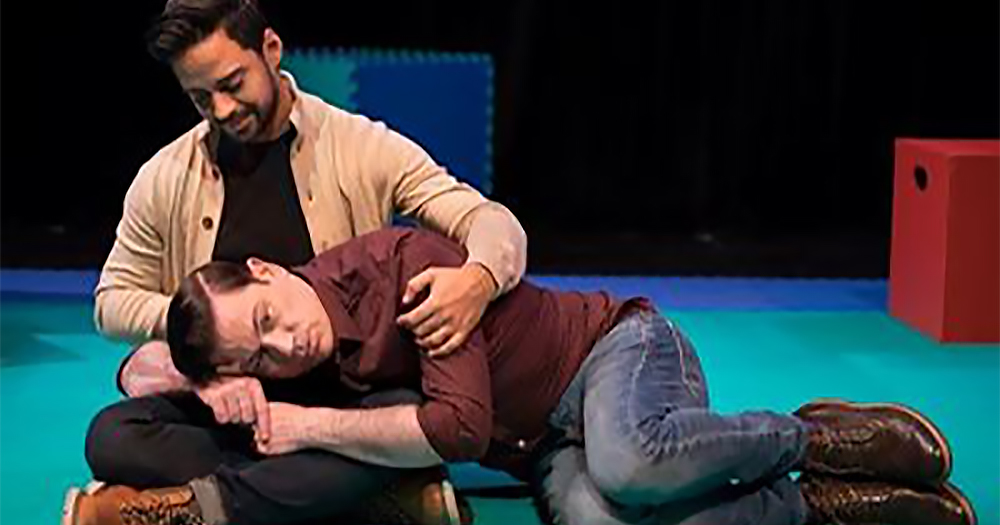 A man lying on the floor, his head resting on another man's lap. This is a moment from the show The Baby Monitor