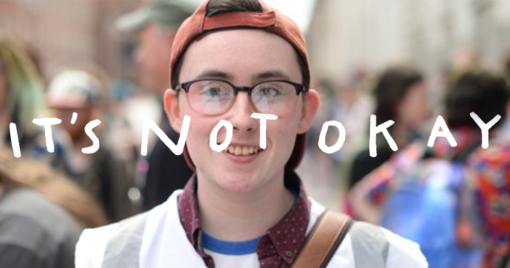 Cameron Keighron, a young trans man, stands on a bus street looking at the camera with the words 'It's not okay' overlaid on the photo