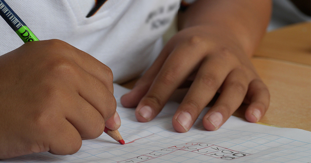 Close up of a child's hand writing a maths problem in a copybook