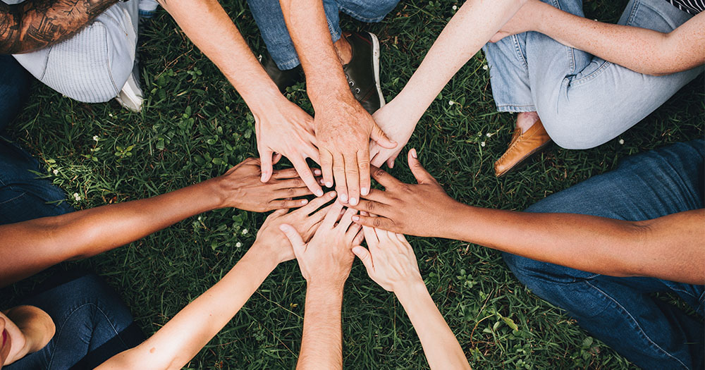 A group of friends in a circle touching hands in the middle