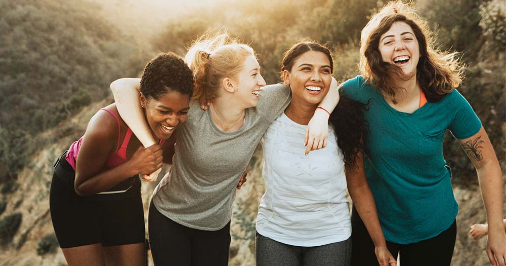 Four laughing women of different races embracing each other