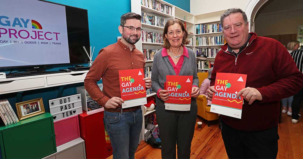 Gay Project Cork launch their publication, two men and a woman hold three of the documents standing in a meeting room