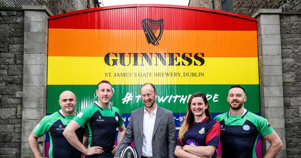 The Guinness brewery gates painted in rainbow colours with four rugby players, one woman, three men, and a man in a suit standing in front