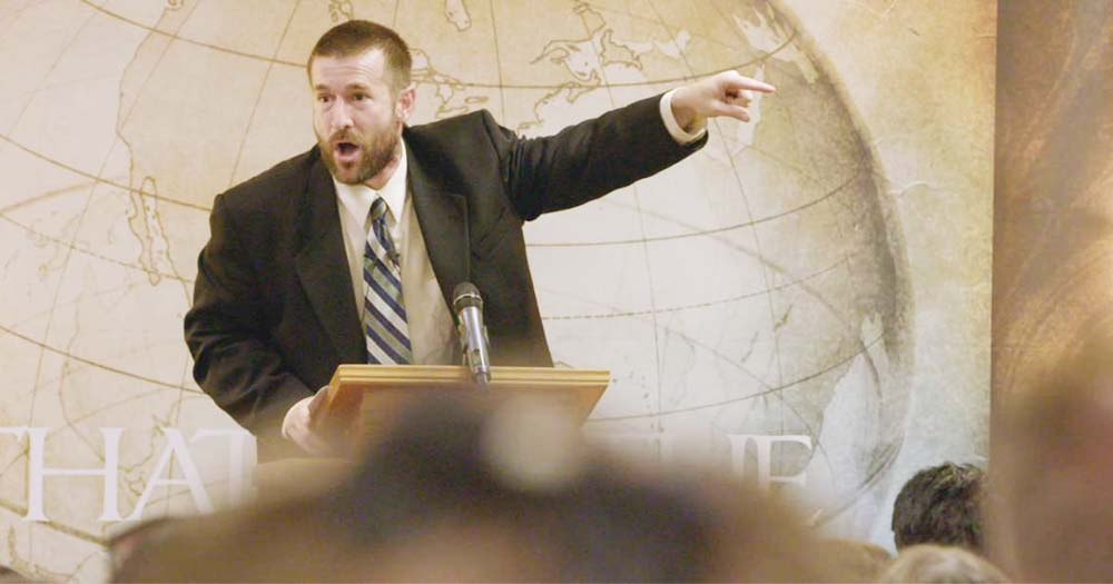 Pastor Steven Anderson shouting and pointing, an image of the globe on the wall behind him