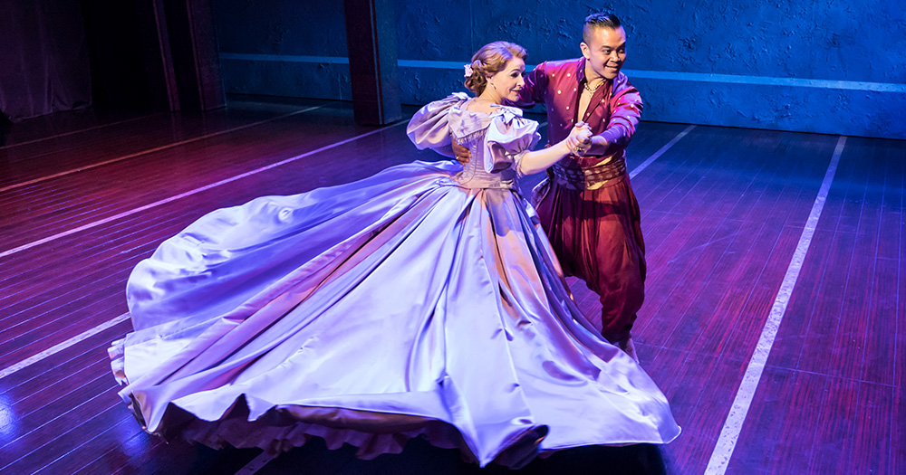 Scene from The King and I featuring a woman in a huge gown and the King of Siam waltzing across the stage