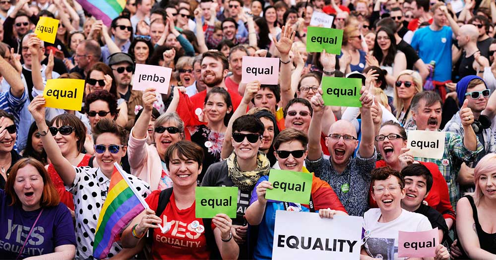 From four years ago - a cheering crowd in rainbow accessories hold up signs celebrating equality