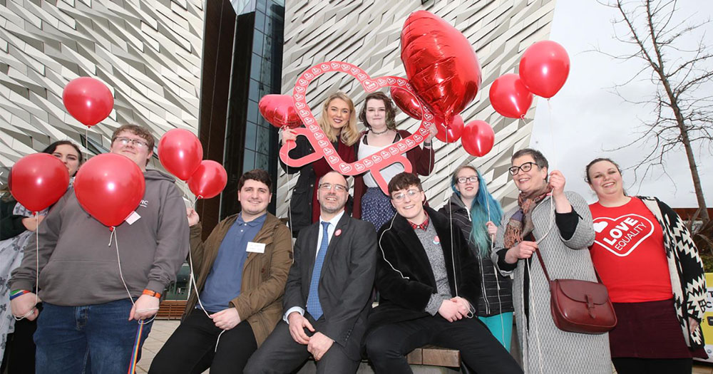 Love Equality campaigners hold heart shaped balloons and banners