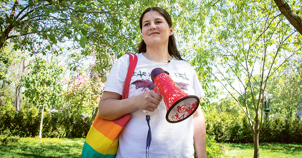LGBT+ rights activist Vitalina Koval in a park, holding a megaphone