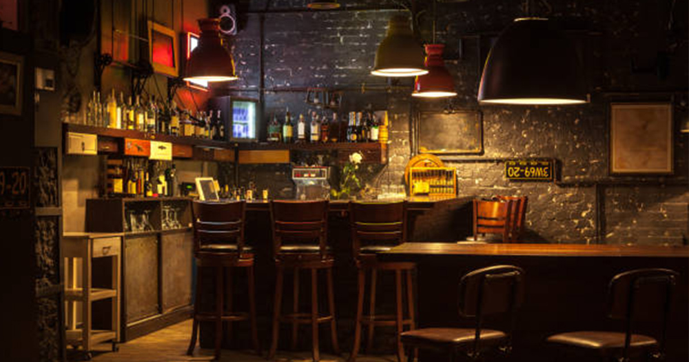 bar with stools in dark lighting with alcohol on shelves behind bar