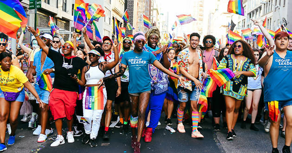 pride parade in New York depicting marching crowd strutting in colourful pride gear
