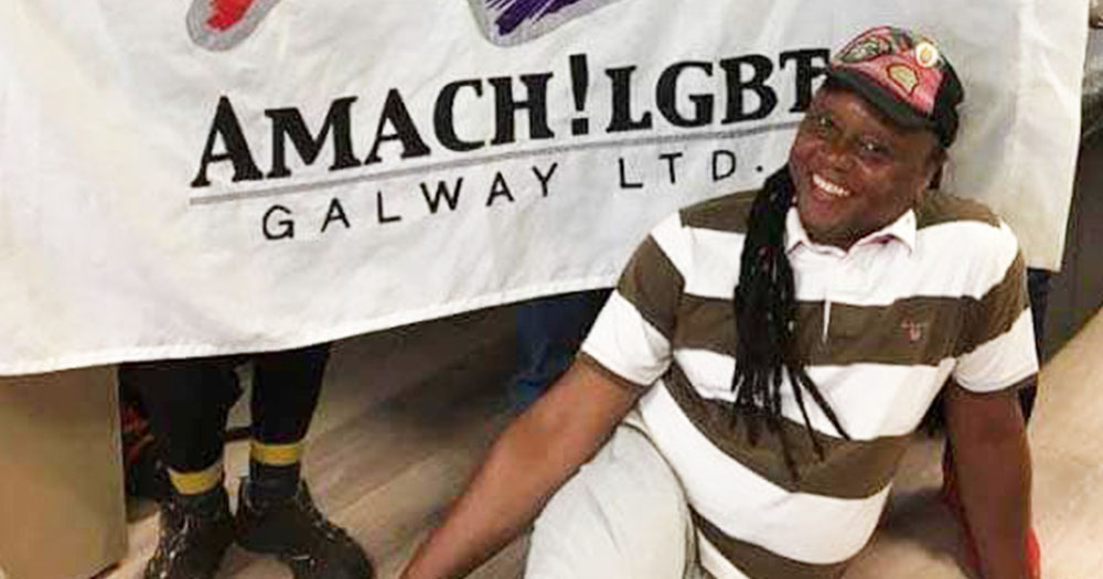 Sylva Tukula wearing a cap sitting on the floor beside a banner for AMACH LGBT