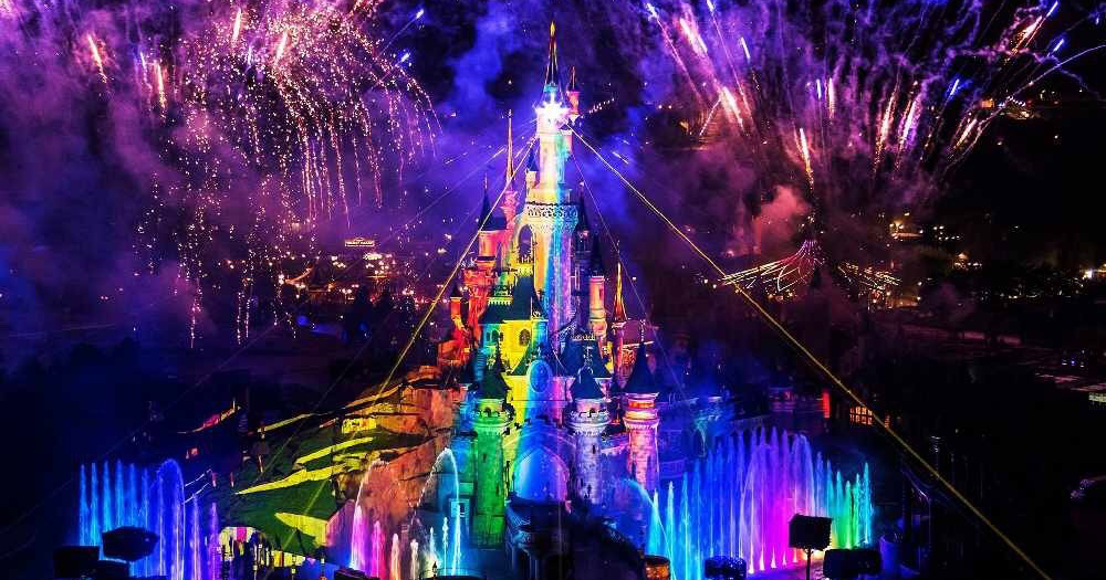 Castle at Disneyland Paris lit up with rainbow colours for Magical Pride