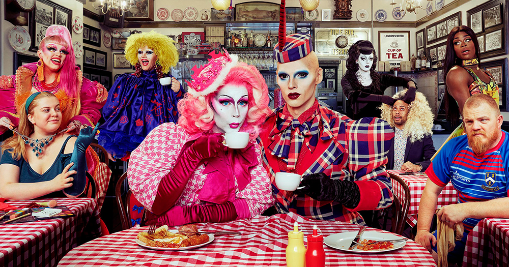 Manchester drag queens of the show Drag SOS sit around a table drinking tea