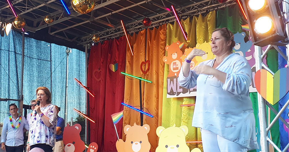 Woman on a stage translating in Irish sign language during Dublin Pride Festival